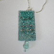 Light turquoise pendant on a chain by textile artist Mary Taylor